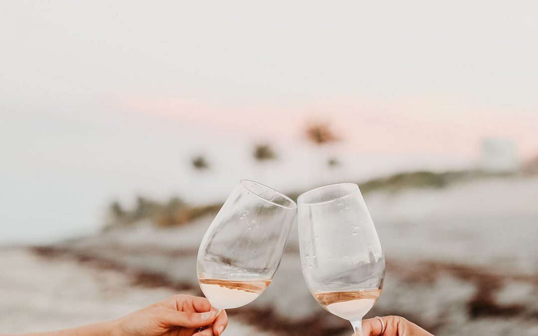 toasting a glass of rose on the beach