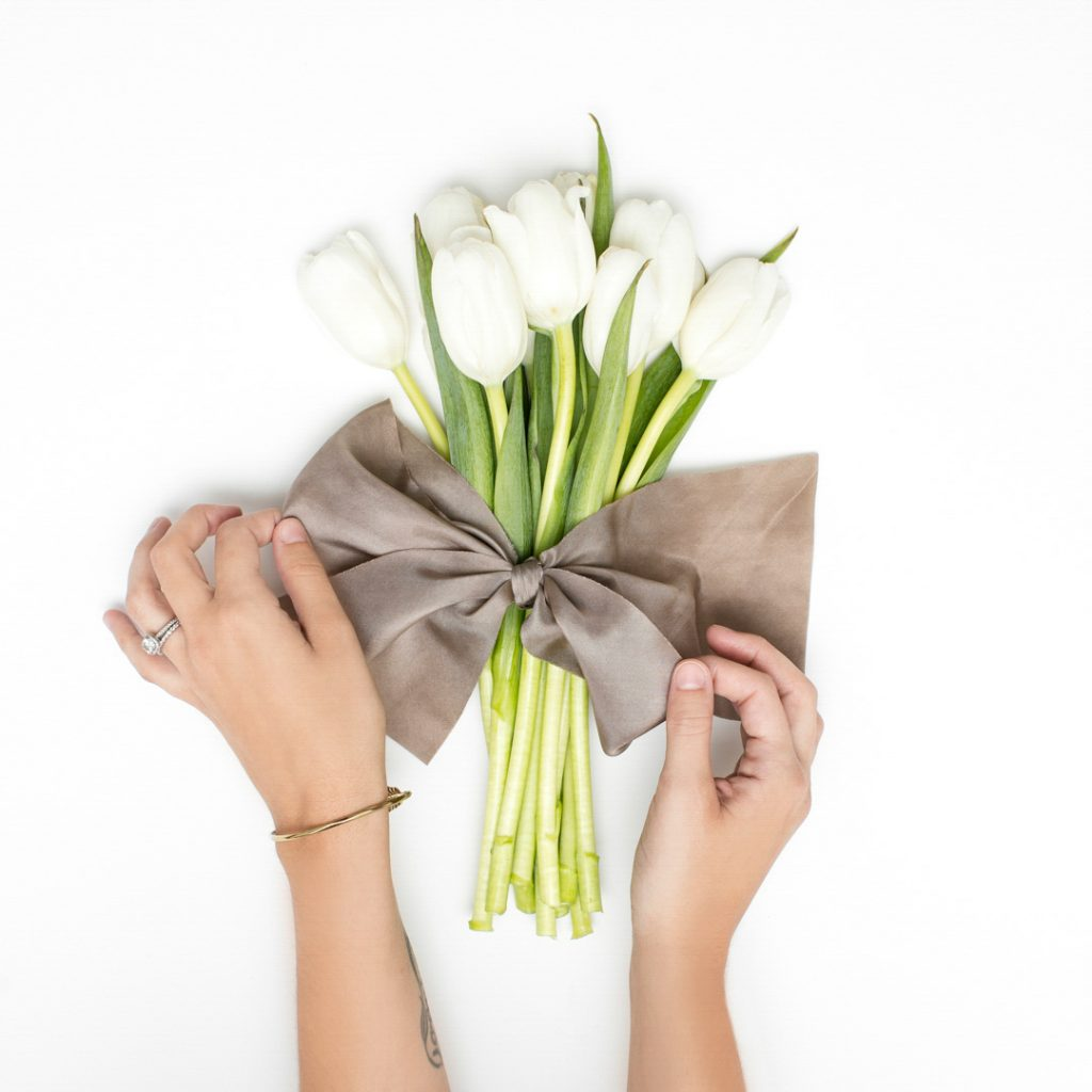 a gift of lillies wrapped in burlap showing tow hands tying a bow around them