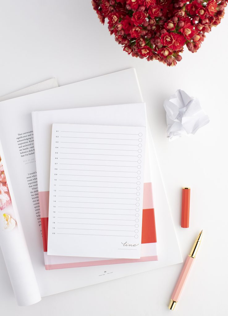 notepad on top of a journal with a pen beside it. red flowers in the background