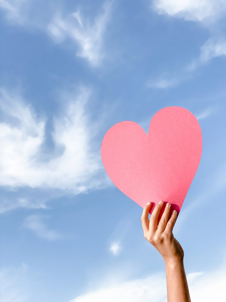 hand holding a pink paper heart into the sky